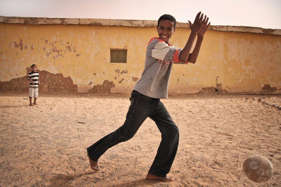 Niño y joven refugiados juegan al fútbol. Al fondo, casa de adobe muy deteriorada. Fotografía tomada en los campamentos de refugiados saharauis