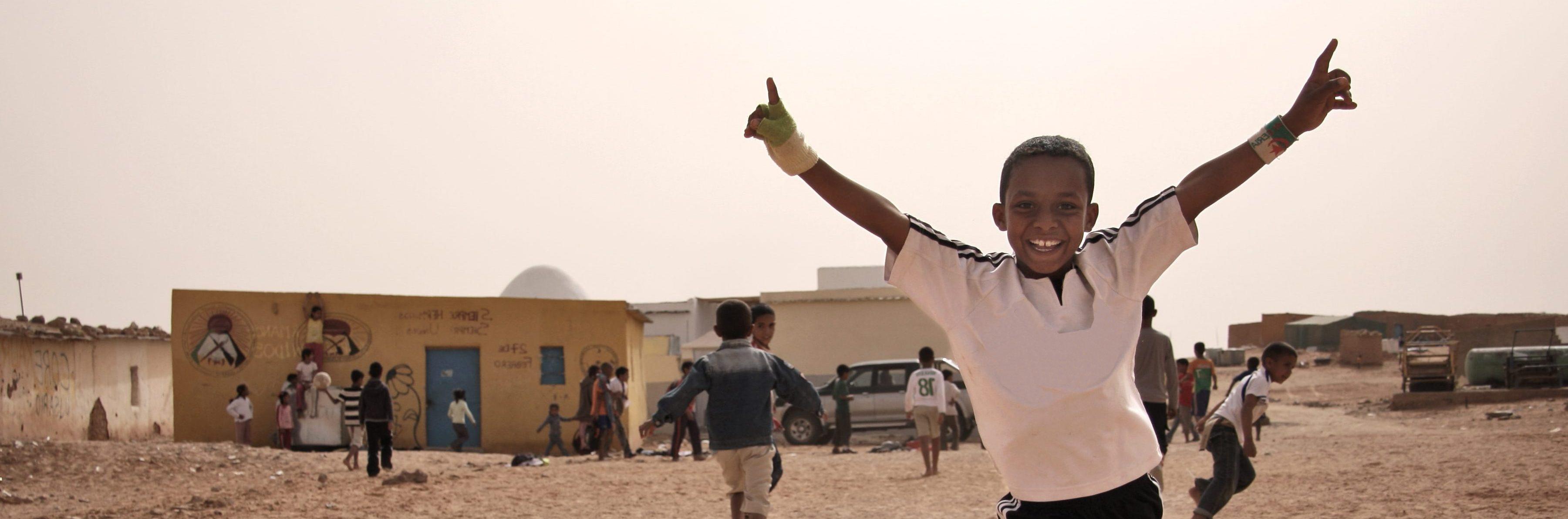 Niños pobres jugando al fútbol. Uno de ellos levanta los brazos en señal de victoria mientras los demás siguen jugando.